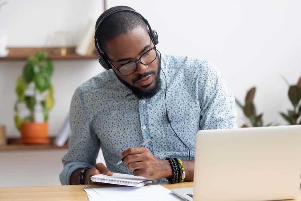 Homem escrevendo em caderno enquanto assiste aula online em seu computador usando fones de ouvido